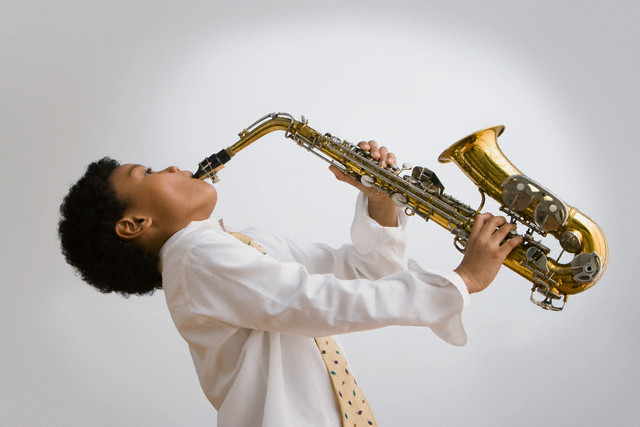 Mixed race boy playing saxophone